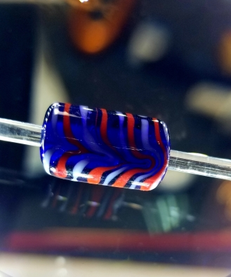 Raked Chevron bead. Size 12-14mm in transparent Dark Blue with opaque red and white chevron design detail. Made by Baroness Maricka Sigrunsdotter, An Tir. Sunna Glassworks.com